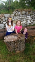 Children playing by wood stump.